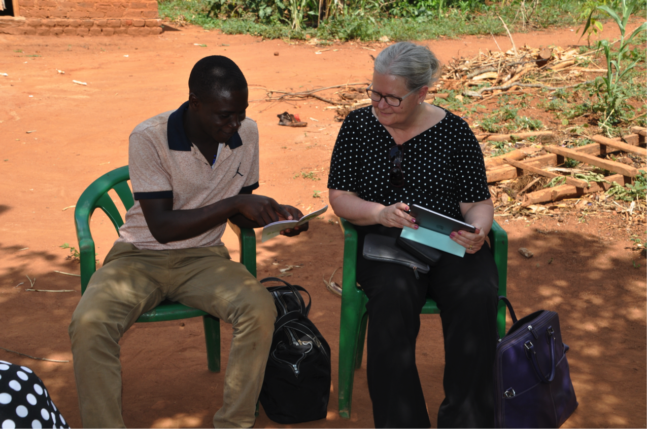 Tony Nyende, L-IFT researcher, explains to Mary Miller about the savings book